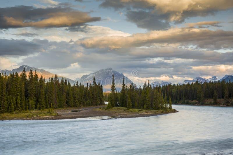 Fiume di Athabasca al tramonto con Rocky Mountains nel fondo fotografia stock