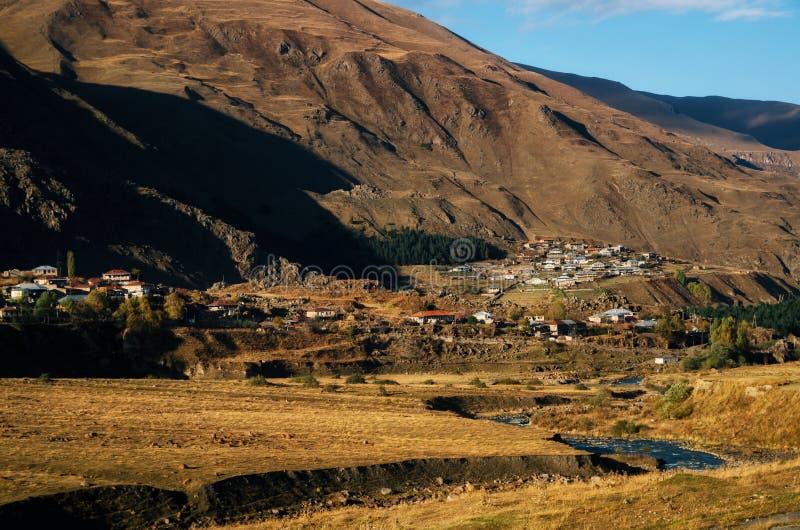 Fiume di Terek contro il villaggio in maggiori montagne di Caucaso, Georgia fotografia stock libera da diritti