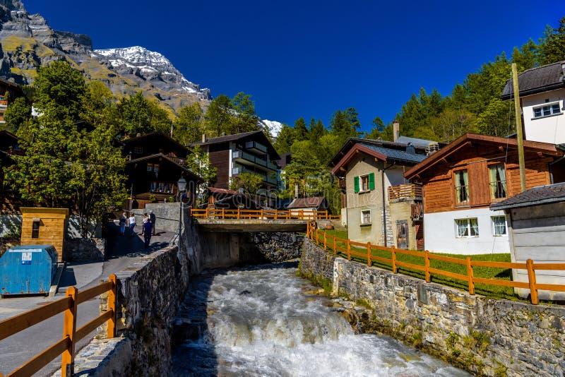 Fiume e chalet in villaggio svizzero in alpi, Leukerbad, Leuk, Visp fotografie stock