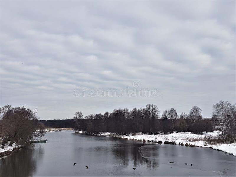 Fiume e neve di inverno contro un cielo blu con le nuvole immagine stock libera da diritti