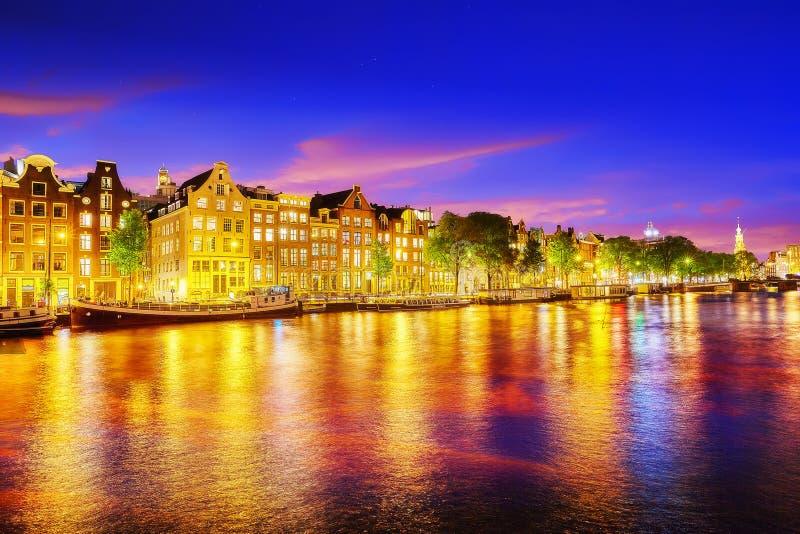 Fiume famoso di Amstel e vista di notte di bella città di Amsterdam immagini stock