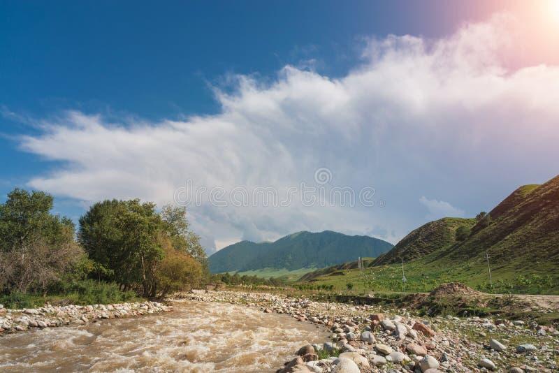 Fiume fangoso di scarico sotto cielo nuvoloso con luce solare fotografia stock