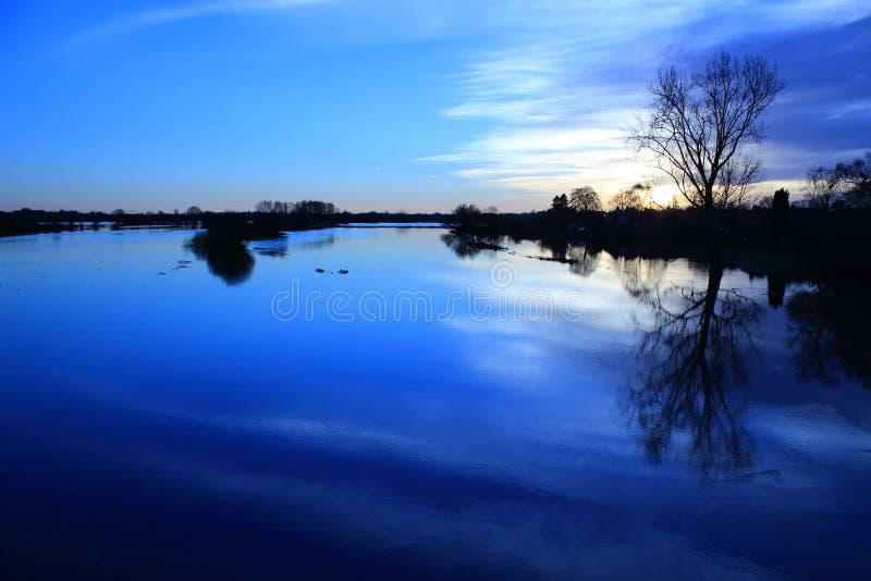 Fiume in inondazione al tramonto fotografie stock