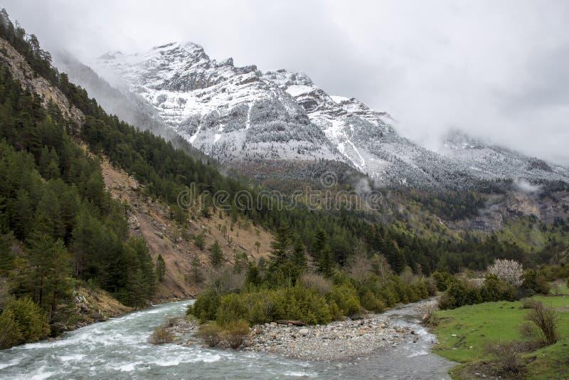 Fiume in valle di Bujaruelo con una certa neve nella montagna, parco nazionale dell'ara di Ordesa y Monte Perdido fotografie stock