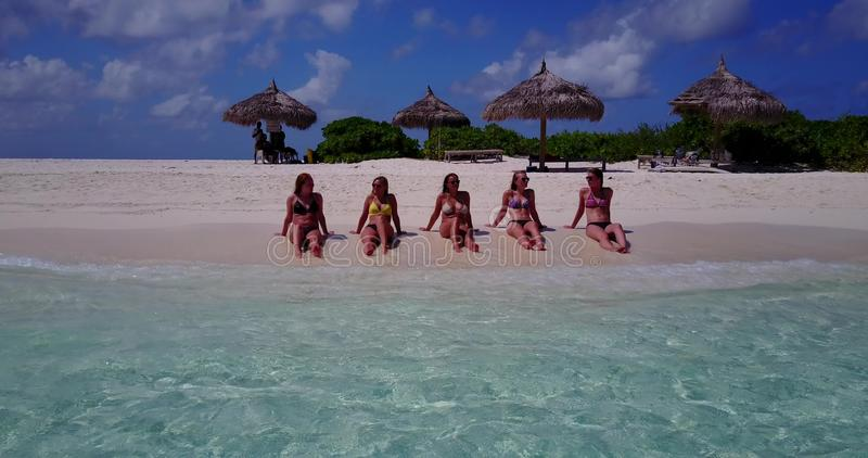 Five 5 beautiful young girls in bikini sunbathing with drone aerial flying view on white sand island sandbank and. Blue sea stock image
