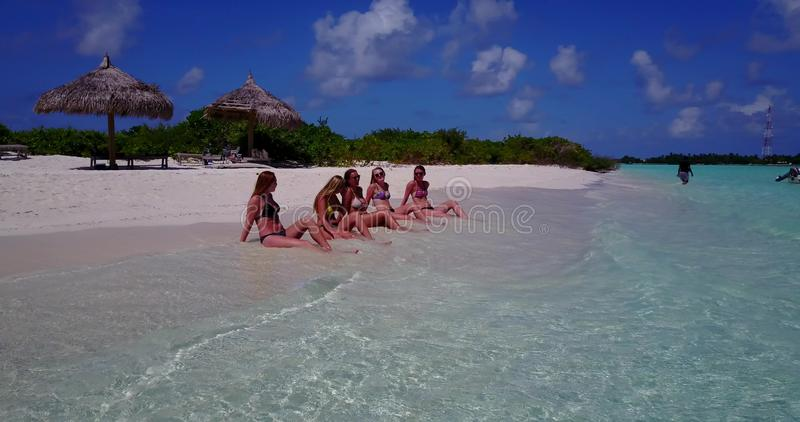 Five 5 beautiful young girls in bikini sunbathing with drone aerial flying view on white sand island sandbank and. Blue sea stock photos