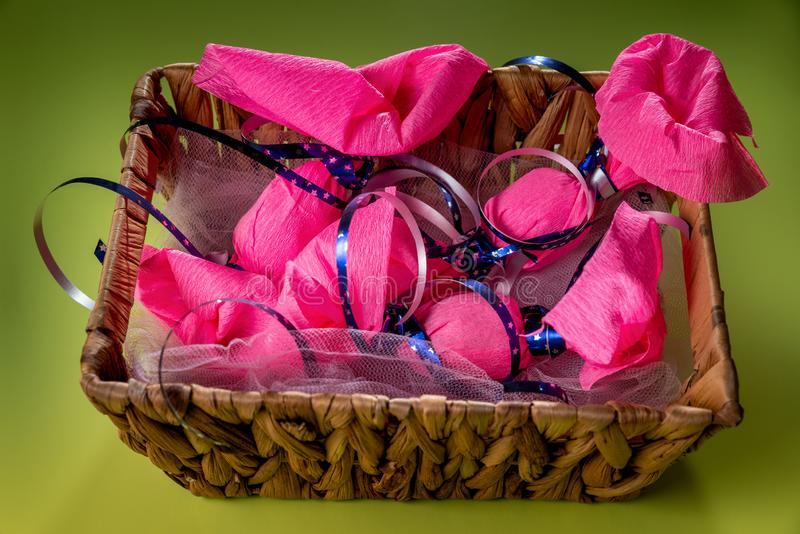 Five big candy wrapped in pink wrap paper with blue ribbon are in brown wicker basket on the green background/table. World Kindnes stock photo