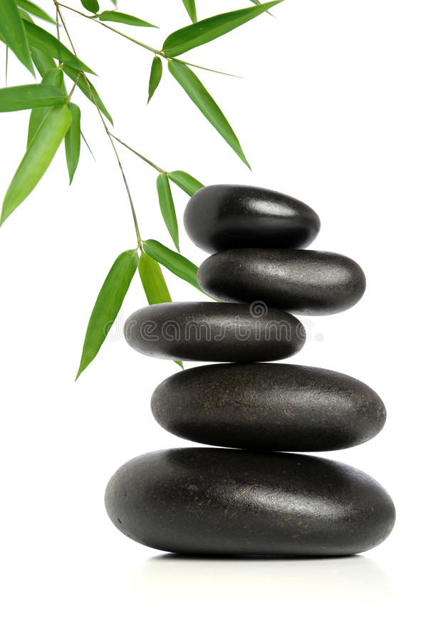 Five Black Stones and Bamboo. Five black stones balanced with bamboo leaves in background stock photography