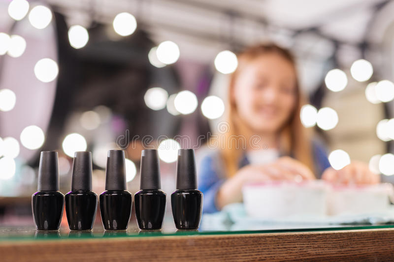 Five bottles of gel nail polish standing on table stock photo