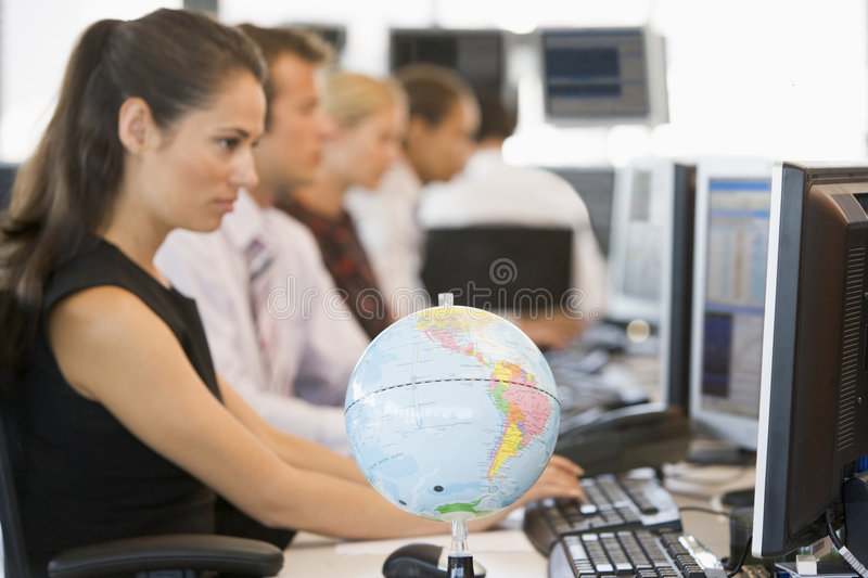 Five businesspeople in office with desk globe stock images