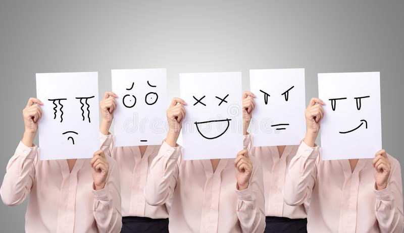 Five businesswoman holding a card with drawing facial expressions different emotion feelings face on white paper stock photo