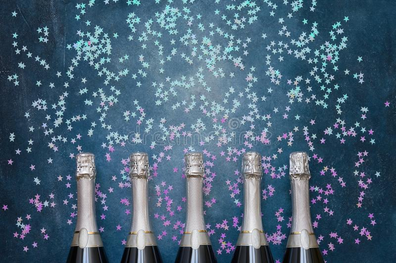 Five Champagne bottles with holographic confetti stars on blue background. Copy space, top view royalty free stock images
