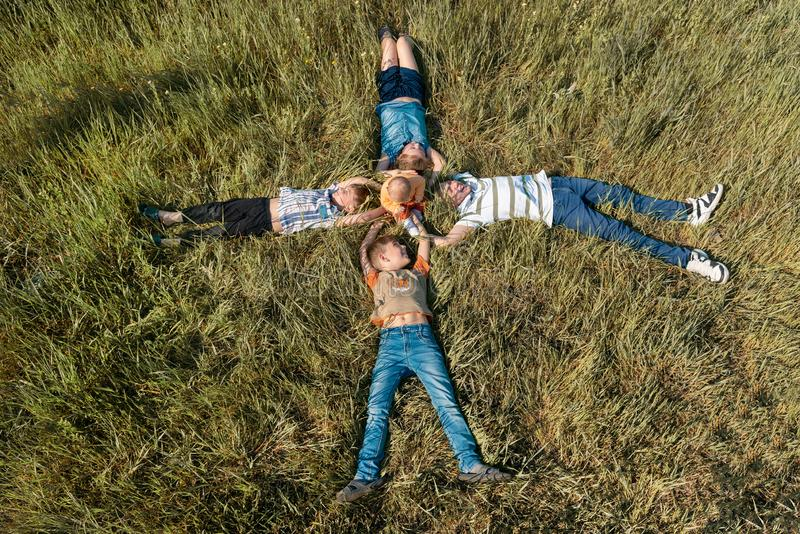 Five children are lying on the grass, a small child is sitting in the center of his brothers and sisters, as seen from above stock images