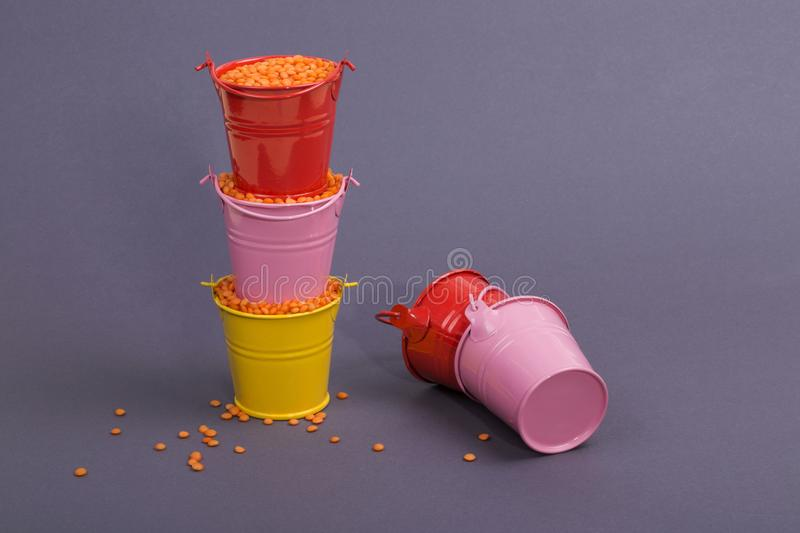 Five colored buckets with lentils beans stock photo