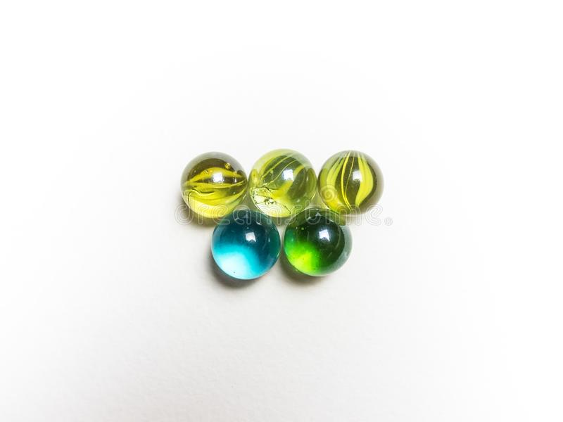 Five colored glass balls with caustics on a white background. Five colored glass balls with caustics on white background stock image