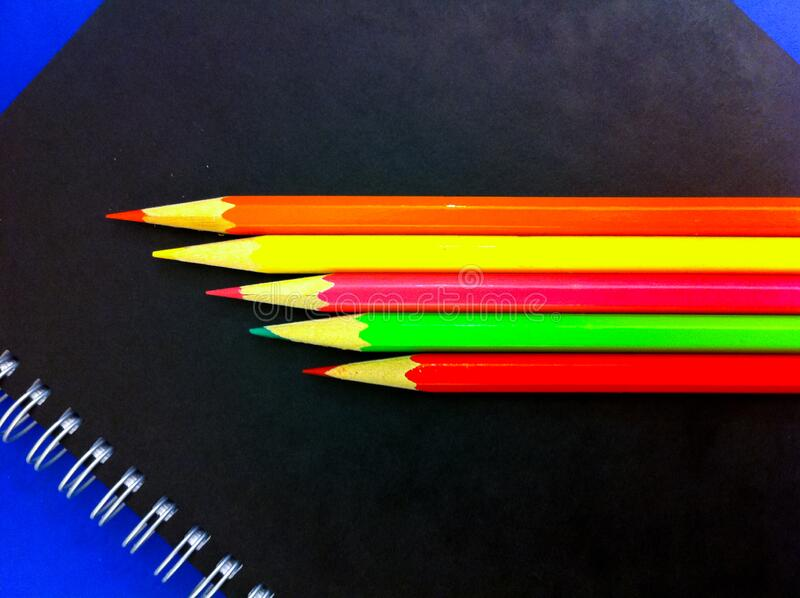Colored pencils and notebook for writing and drawing stock photo