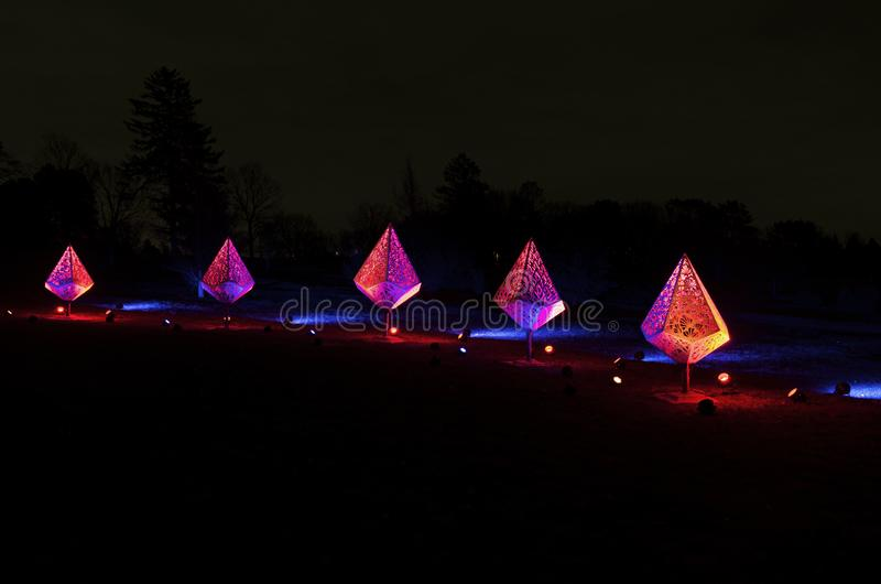Five Colorful Fixtures and Spotlights in Park. Five decorative fixtures illuminated by colorful floodlights in park during holidays royalty free stock photo