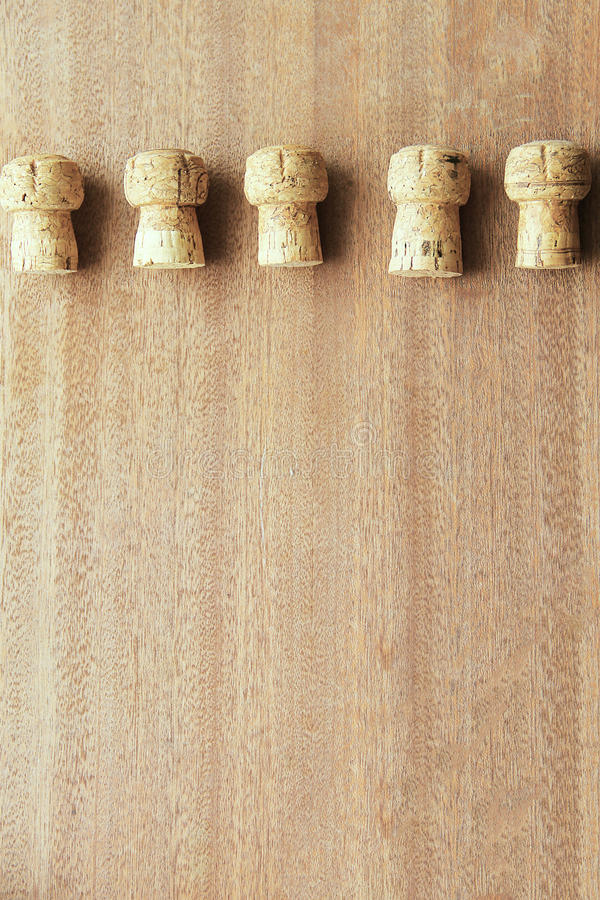 Five corks from champagne cork oak lined in a row on top of the wooden board.  stock image