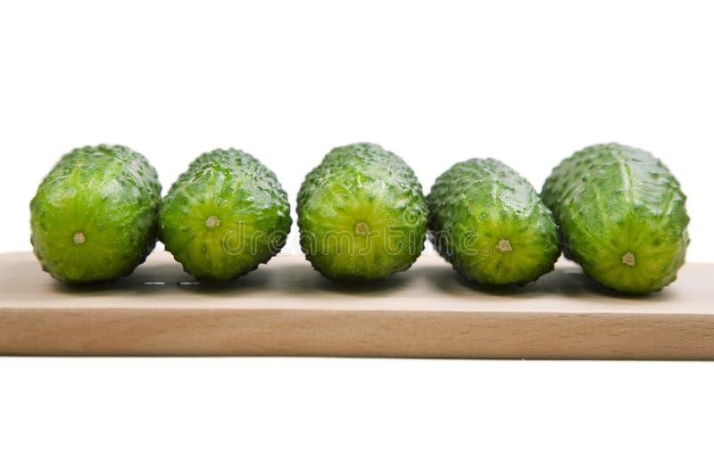 Five cucumbers laying on cutting board