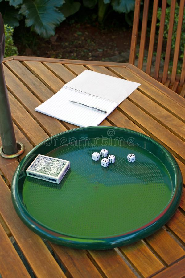 Five 5 dice lying on tray with notebook and pen on wooden table plus a deck of cards stock image