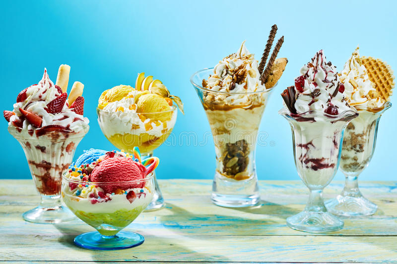 Five different flavor ice cream sundaes. On light wooden table with blue background stock photography