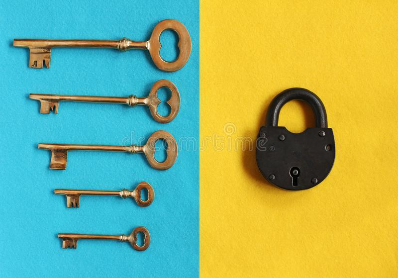 five different golden keys on blue felt and close padlock on yel stock photography