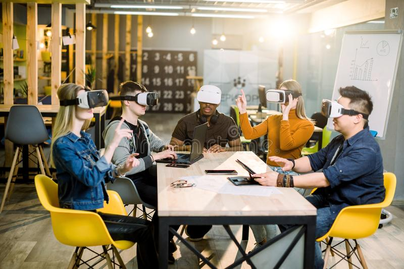 Five diverse business persons are developing a project using virtual reality goggles. the concept of technologies of the royalty free stock photo
