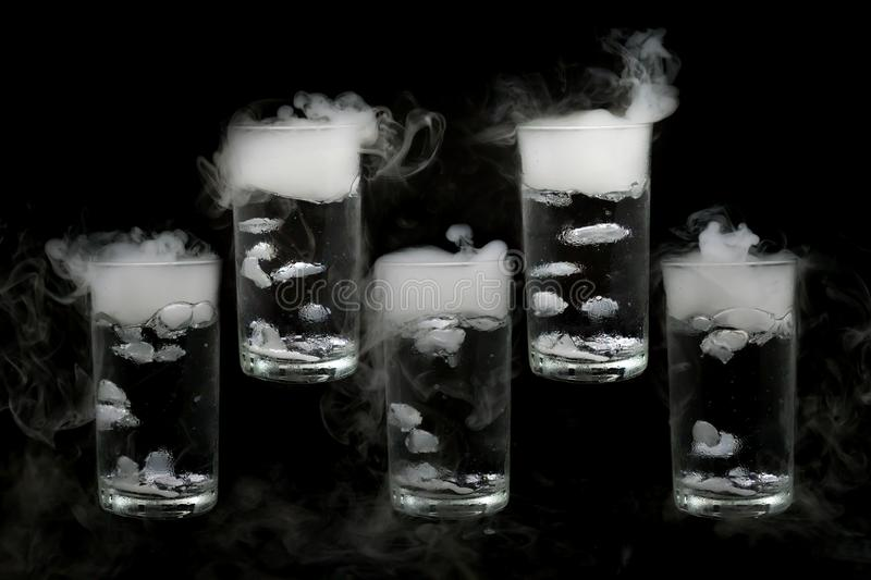 Five dry ice in a glass of water isolated on black background. Smoke, Close up royalty free stock photo