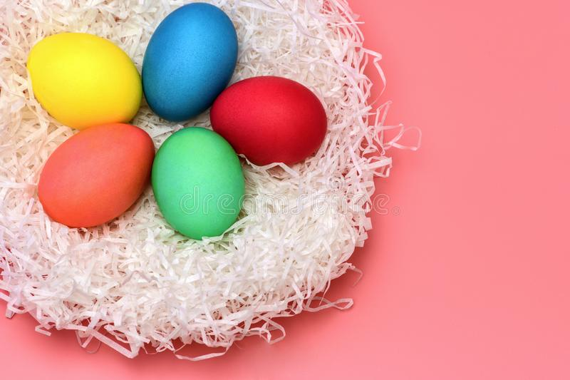 Five Easter colored eggs lie in the nest on a gently pink background, top view. stock image