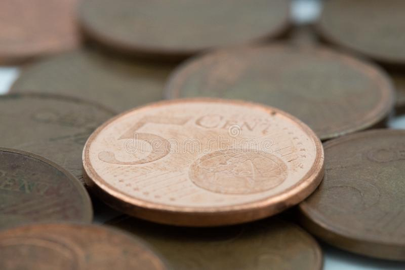 Five euro cent coin supported on more bronze coins royalty free stock photography