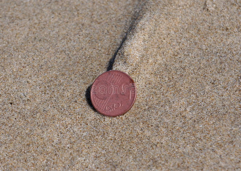 Five Euro cents. A five Euro cents coin on the beach, ready for a beachcomber to find royalty free stock image