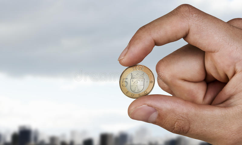 Five euro coin between fingers stock photography
