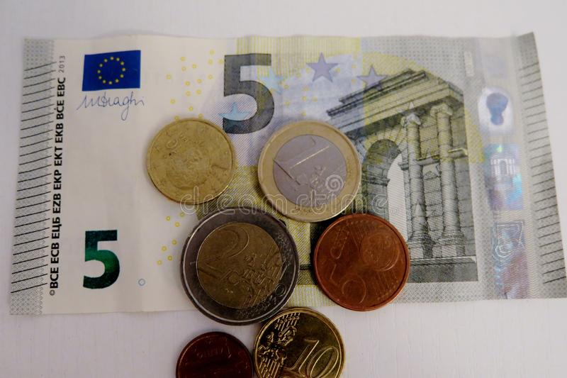 Five euro and a penny on a white background close-up stock images