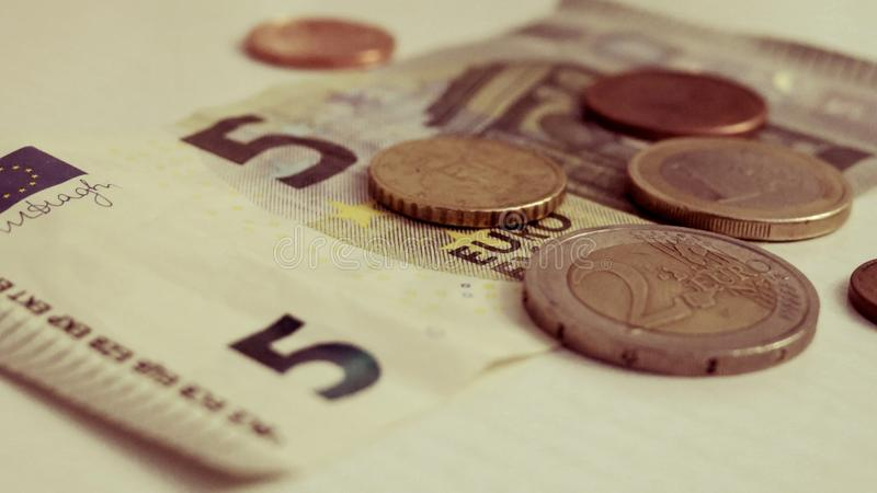 Five euro and a penny on a white background close-up stock photos