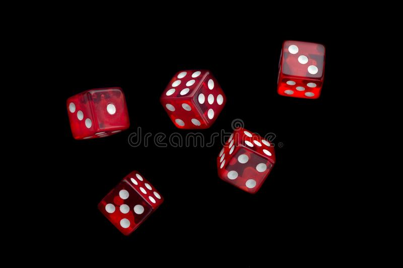 Five falling translucent red dices on black background stock photos