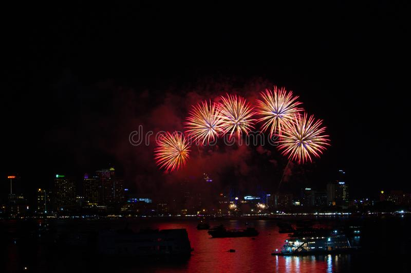 five fireworks on beach and reflection color on water surface stock image