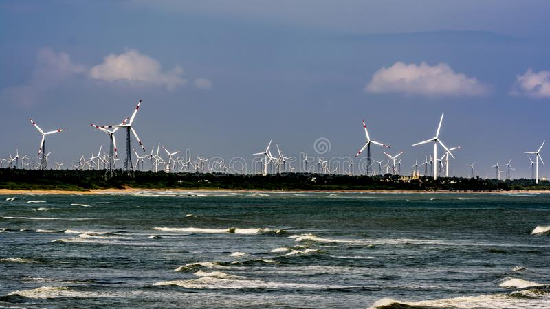 Five Forces of Our world: Wind, Sun, Water, Land and Sky. Arrangement of wind turbines on a Seashore, juxtapositioned with trees/vegetation and the waves in stock image