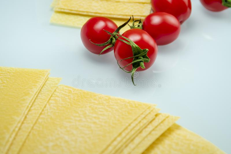 Tomatoes between lasagna on white reflexive glass royalty free stock photos