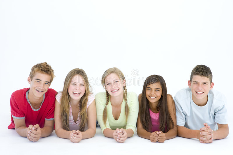 Five friends lying down in a row smiling royalty free stock image