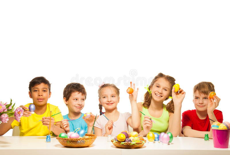 Five funny children with colourful Eastern eggs stock photo