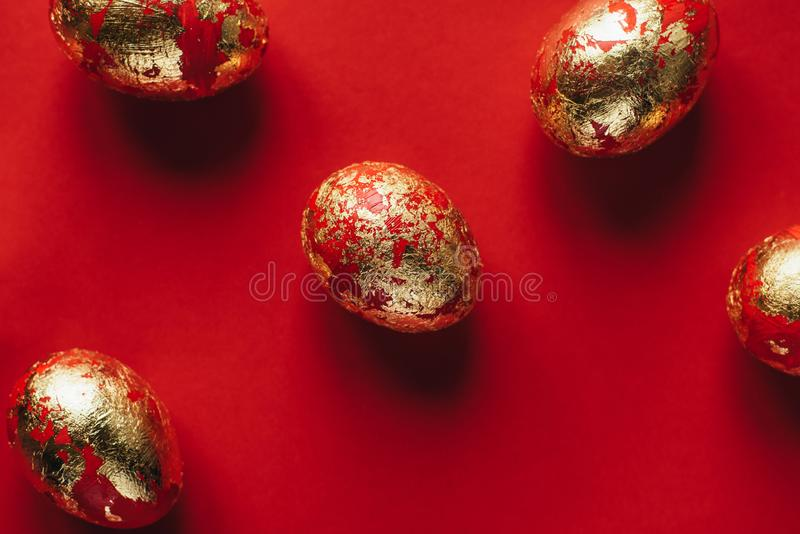 Five golden colored and decorated with sparkles Easter eggs on red background. stock photo