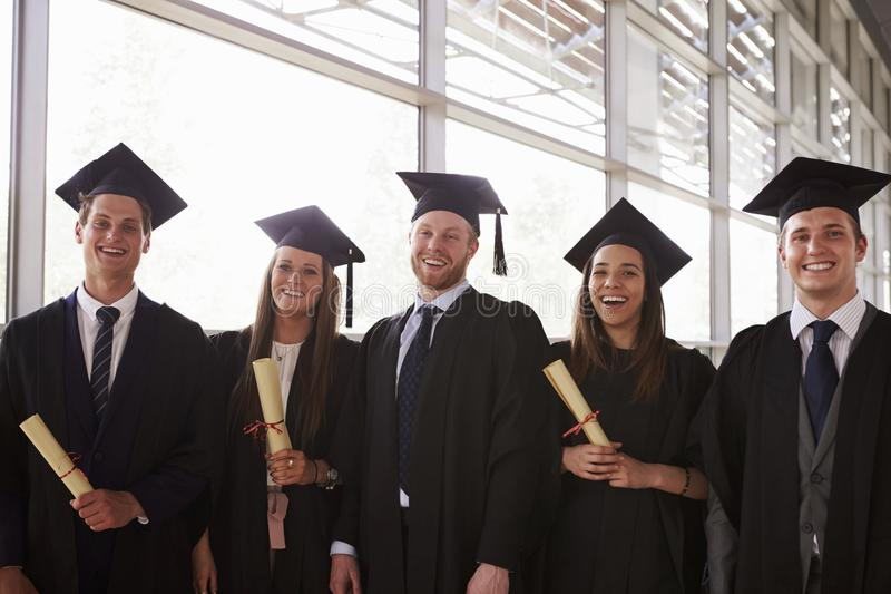 Five graduates in mortars and gowns holding certificates stock photos
