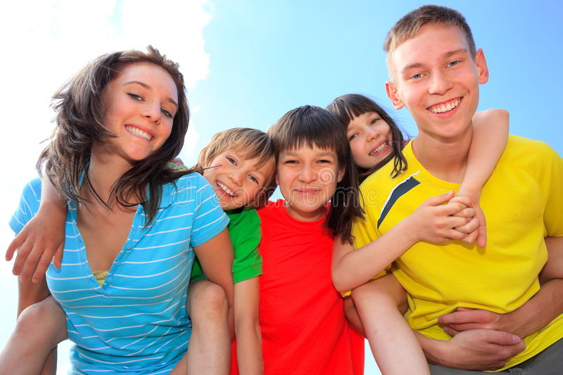 Five happy children. Happy brothers and sisters in a close knit group active and laughing royalty free stock photos