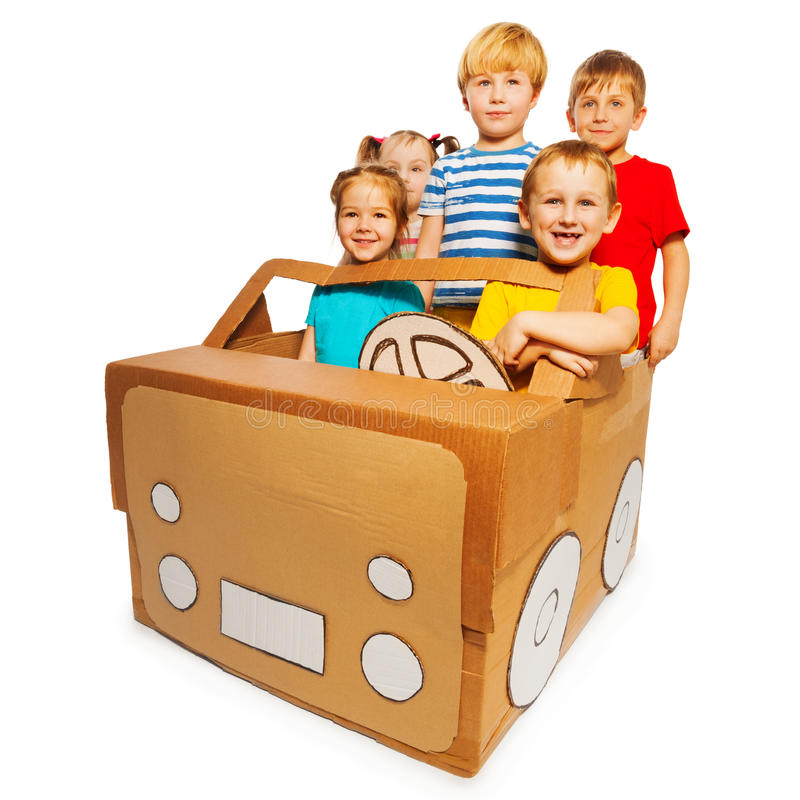 Five happy children driving handmade cardboard car stock images