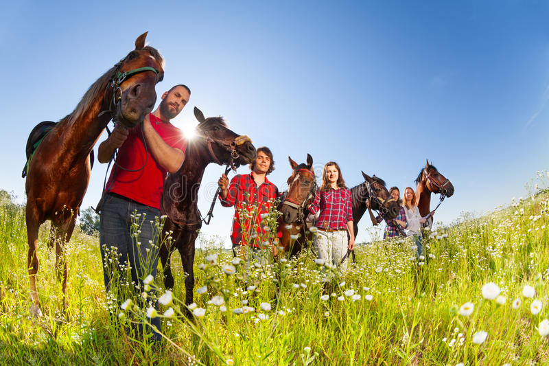 Five happy equestrians walking with their horses. Five happy equestrians walking across the blossoming meadow with their horses in sunny day royalty free stock photography
