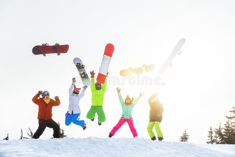 Five happy friends snowboarders jumps and having fun stock images