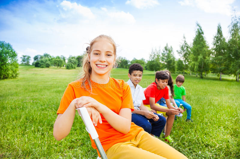Five happy kids sit on chairs in row outdoors royalty free stock images