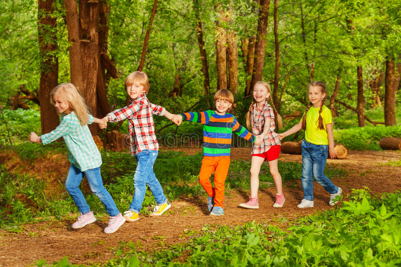 Five happy kids walking in forest holding hands royalty free stock photos