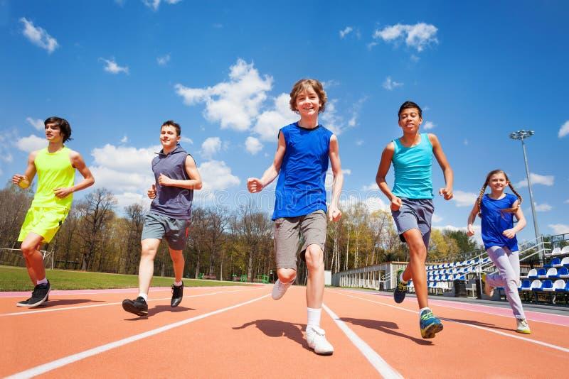 Five happy teenage kids running on the stadium. Group of five happy teenage kids in sportswear, running on the stadium on sunny day stock image