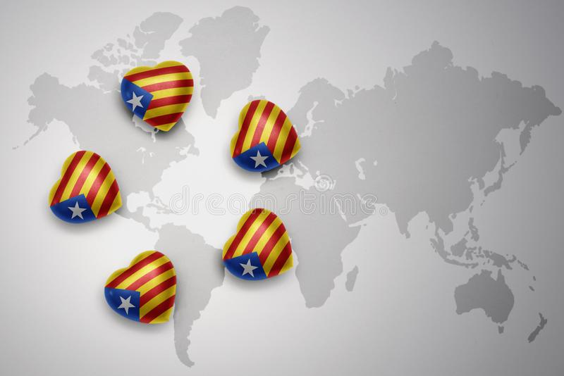 five hearts with national flag of catalonia on a world map background. stock illustration